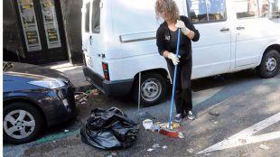Una mujer limpia frente a su tienda. (Archivo)
