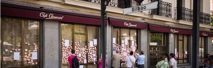 Varios viandantes observan los papeles con recuerdos y reivindicaciones pegados en los escaparates del Café Comercial.