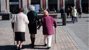 Dos ancianas dependientes con una persona que las ayuda ante la estación de Principe Pio. (Archivo)