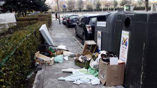Restos de todo tipo de basura junto a contenedores de reciclaje