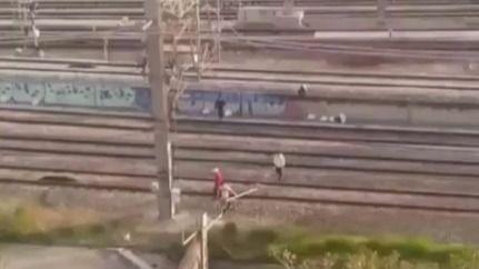 Un grupo de jóvenes cruza las vías del tren de Atocha por un paso no habilitado
