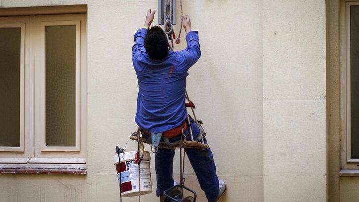 Un hombre trabaja en la fachada de un edificio.