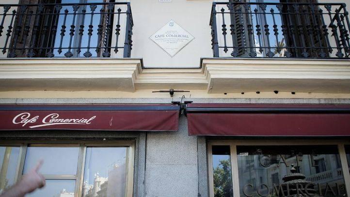 Un cliente diario del Café Comercial señala la placa conmemorativa que indica que estuvo abierto desde 1887.