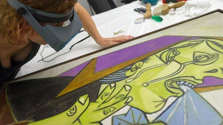 Una restauradora observa con gafas de aumento los trazos de un cuadro de Picasso en el taller de restauración.