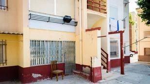 Uno de los portales de las viviendas no rehabilitadas en la calle Guadalaviar.