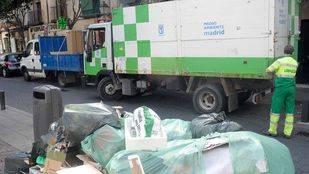Camion de la basura y operarios recogen monton generado de basura