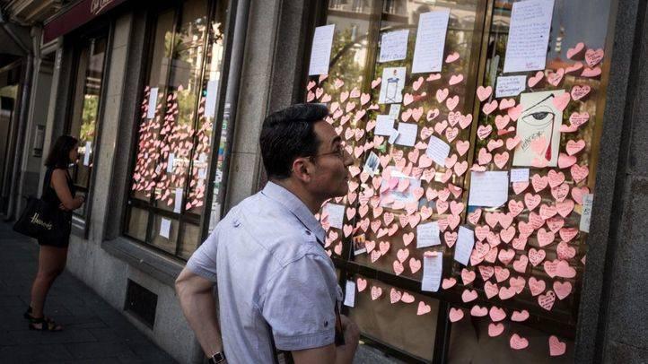 Un hombre mira un dibujo de un ojo llorando sangre por el cierre del Café Comercial.