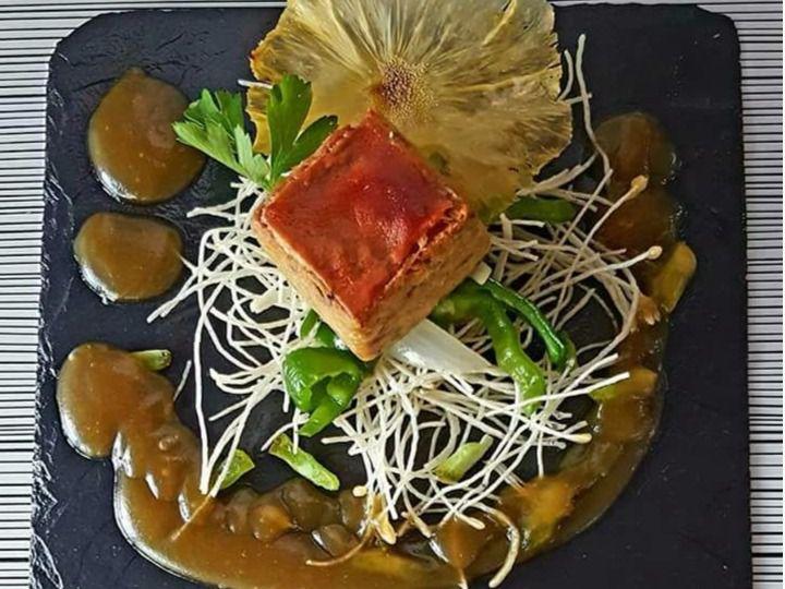 Propuesta del Bar Restaurante Sevilla de tapa de cochinillo confitado con canela sobre fondo de su misma salsa con pasas y piel crujiente