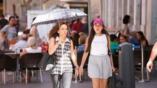 Una mujer se protege del sol mientras camina por el centro de la ciudad.