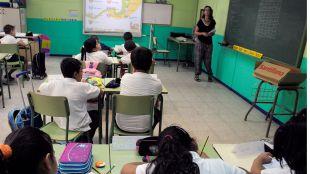 Una clase de primaria y su profesora en una foto de archivo.