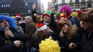 Cientos de personas preparan la despedida del año celebrando las 'preuvas' en la Puerta del Sol