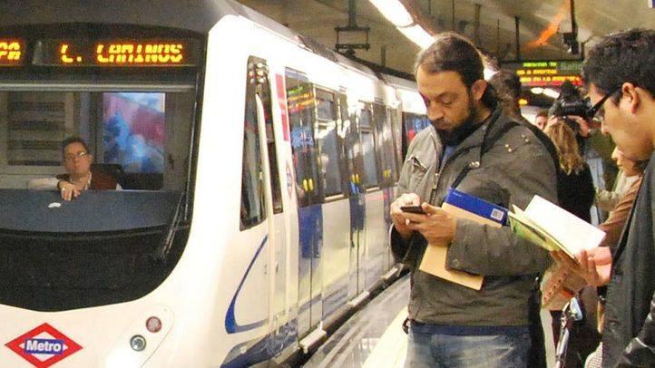 Un viajero del Metro mira su telefono móvil.