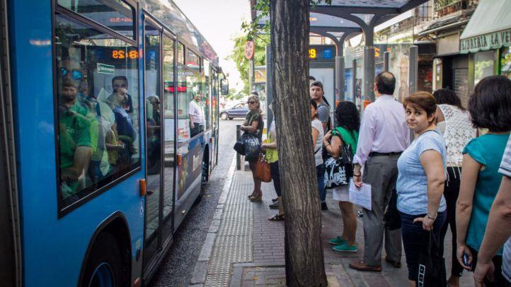 Foto de archivo de varias personas esperando en una parada de autobús.