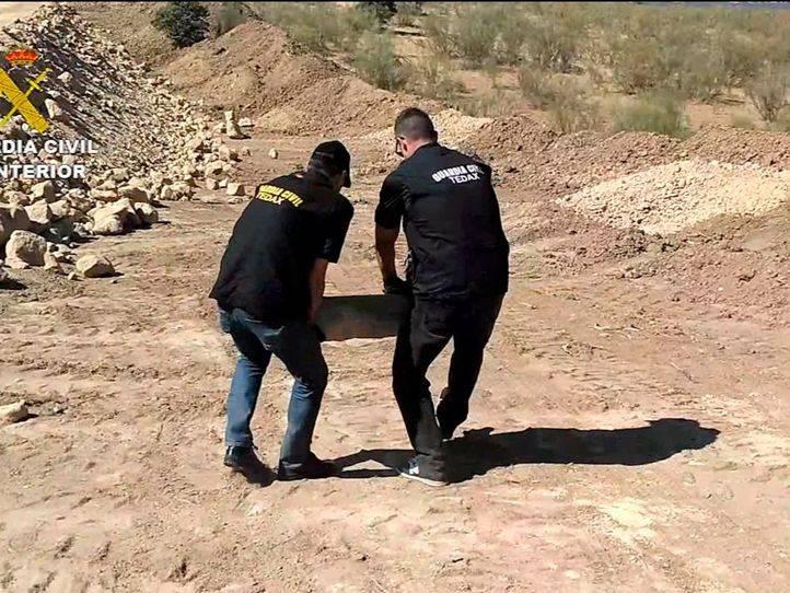 Dos agentes de la Guardia Civil portan una bomba de la Guerra Civil hallada en Boadilla para su desactivación y destrucción controlada
