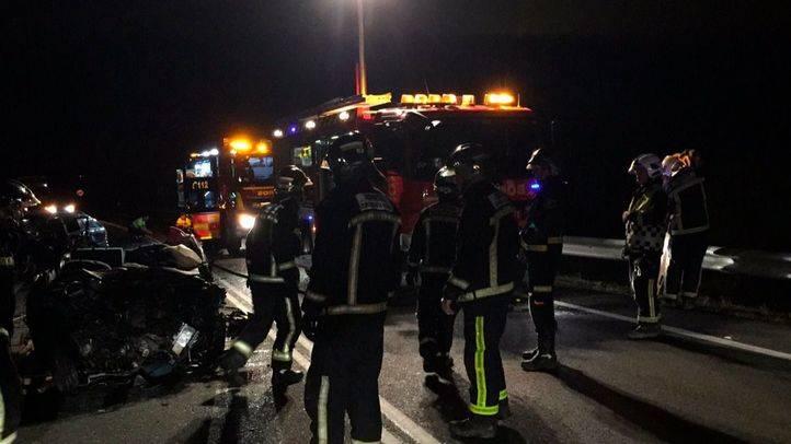 Bomberos trabajan para rescatar el cuerpo del fallecido en un accidente en la M-100 a la altura de Daganzo