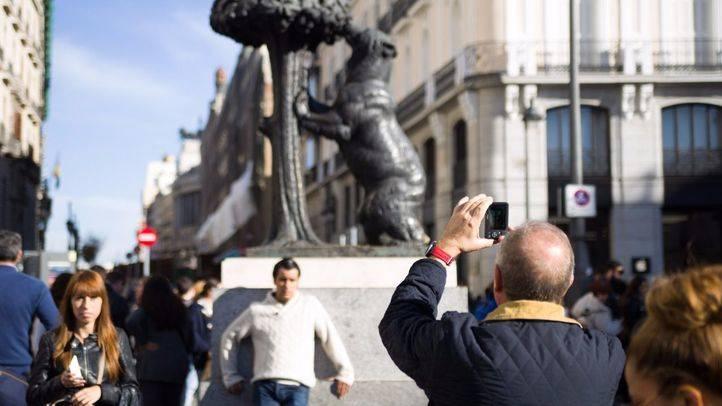 Turistas fotografiándose junto a la estatua del oso y el madroño, en la Puerta del Sol.