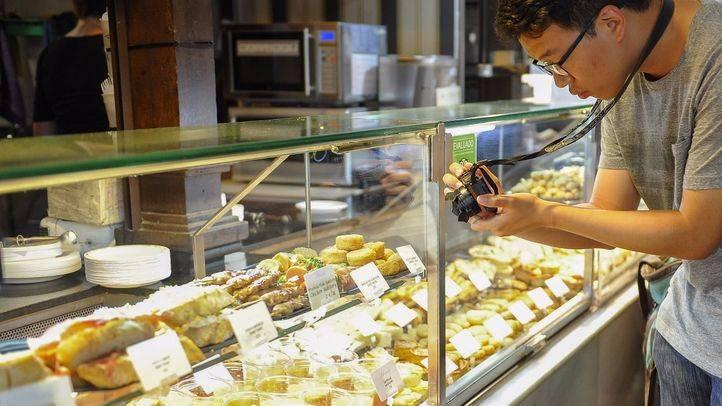 Un turista fotografía quesos en un mercado gastronómico de Madrid.