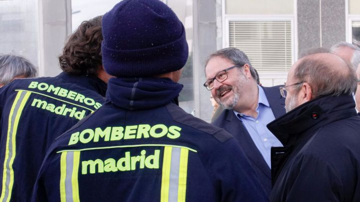 Barbero saluda a dos bomberos municipales.