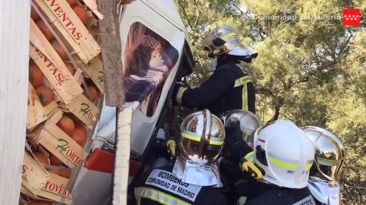 Los bomberos intentan liberar a uno de los conductores que se han visto implicados en la colisión.