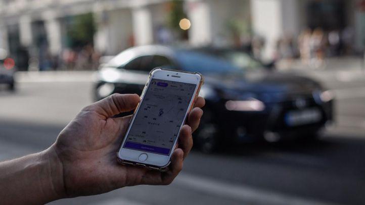 Un usuario de Cabify busca vehículos de transporte con conductor en la Gran Vía.