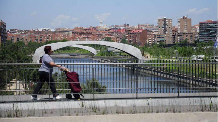 Una mujer con carrito cruza el puente de Legazpi sobre el Manzanares. Al fondo, Madrid Río.