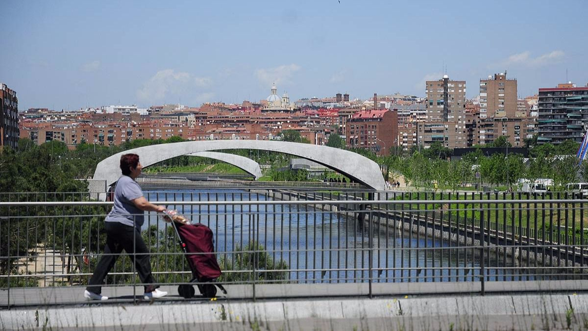 Una mujer con carrito cruza el puente de Legazpi sobre el rio Manzanares al fondo Madrid-Rio y edificios.