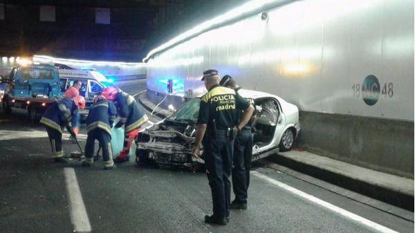 Bomberos trabajando tras salir heridas dos personas en un choque frontal de dos vehículos en la Calle 30.