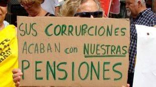 Una mujer participa con una pancarta en las marchas por las pensiones públicas que confluyen este lunes en Madrid