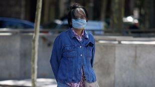 Una turista japonesa con mascarilla para evitar la contaminación atmosférica en el paseo de la Castellana.