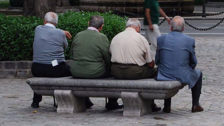 Foto de archivo de varias personas mayores sentadas en un banco.