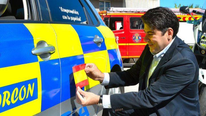 David Pérez pega una bandera española en un coche de la Policía Local
