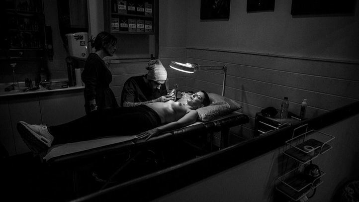 Alvaro tatúa sobre el pecho de Beatriz, que a sus 37 años ha superado un cáncer en cada pecho y dos intervenciones quirúrgicas.