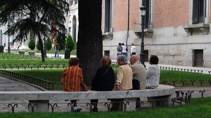 Personas mayores sentadas en un banco de piedra en el Museo del Prado
