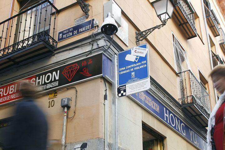Una cámara de videovigilancia con cartel de aviso en la esquina de la calle Mesón de Paredes