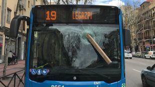 Un hombre lanza un tablón de madera contra la luna de un autobús de la EMT