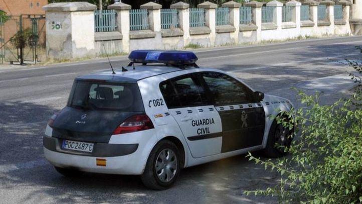Un guardia civil de trafico y su coche en una carretera comarcal de Madrid