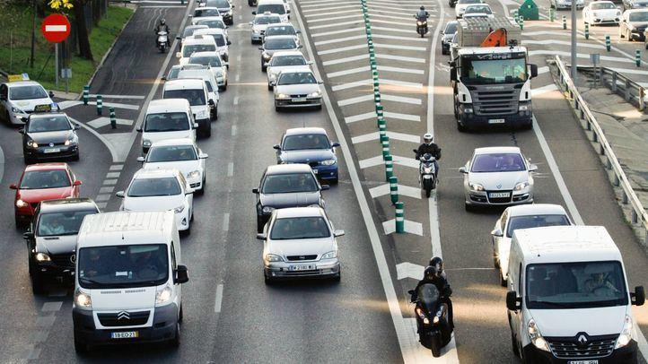 Gran acumulación de tráfico rodado de coches turismos en la carretera de circunvalación M30 y motos por el arcén..