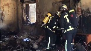 Los bomberos intervienen en la vivienda incendiada.