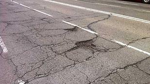 Desperfectos en el asfalto y las aceras de la calle Ermita del Santo.