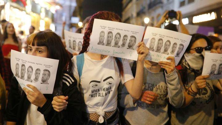 Manifestantes se tapan la cara con un cartel que muestra las de La Manada.