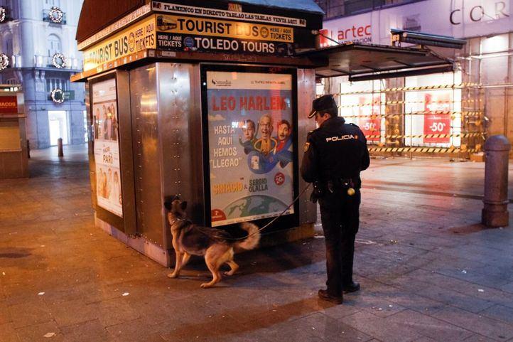 Un agente de Policía junto a un kiosko de prensa.