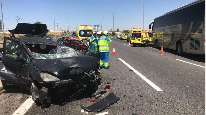 Uno de los coches implicados en el accidente, junto a otro y al autocar.