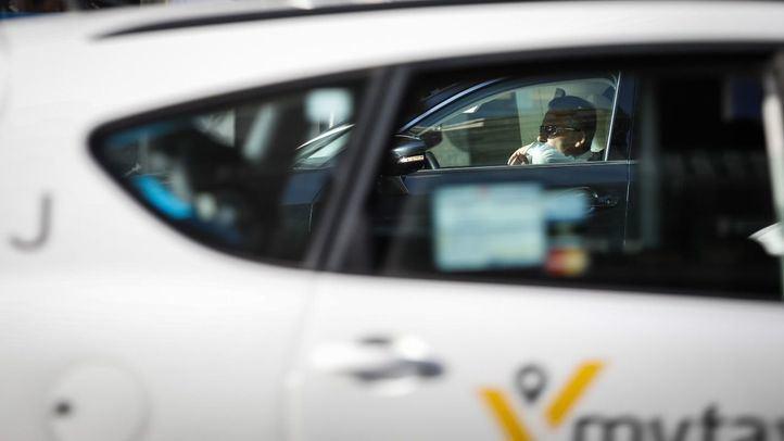 Un conductor de VTC a través de la ventanilla trasera de un taxi en la Gran Vía madrileña.