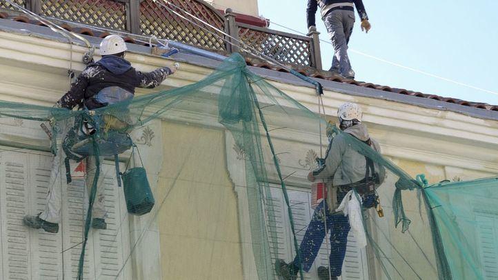 Obreros trabajando en altura en una foto de archivo.