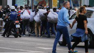 Imagen de archivo de un policía junto a un grupo de manteros en la Gran Vía.