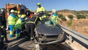 Los bomberos y sanitarios trabajan para liberar al conductor atrapado tras la colisión.