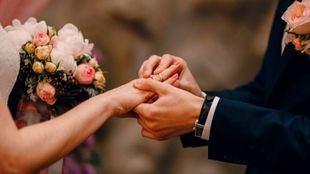 Una pareja de novios se intercambia las alianzas de boda.