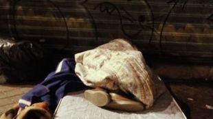 Imagen de archivo de una persona sin hogar durmiendo en la calle.