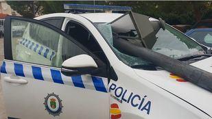 Coche de la policía que colisionó contra una farola por el efecto rebote del otro coche.