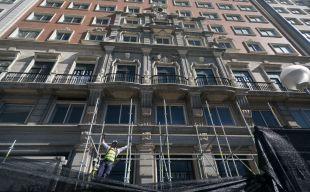 Operario montando andamios en la fachada principal.